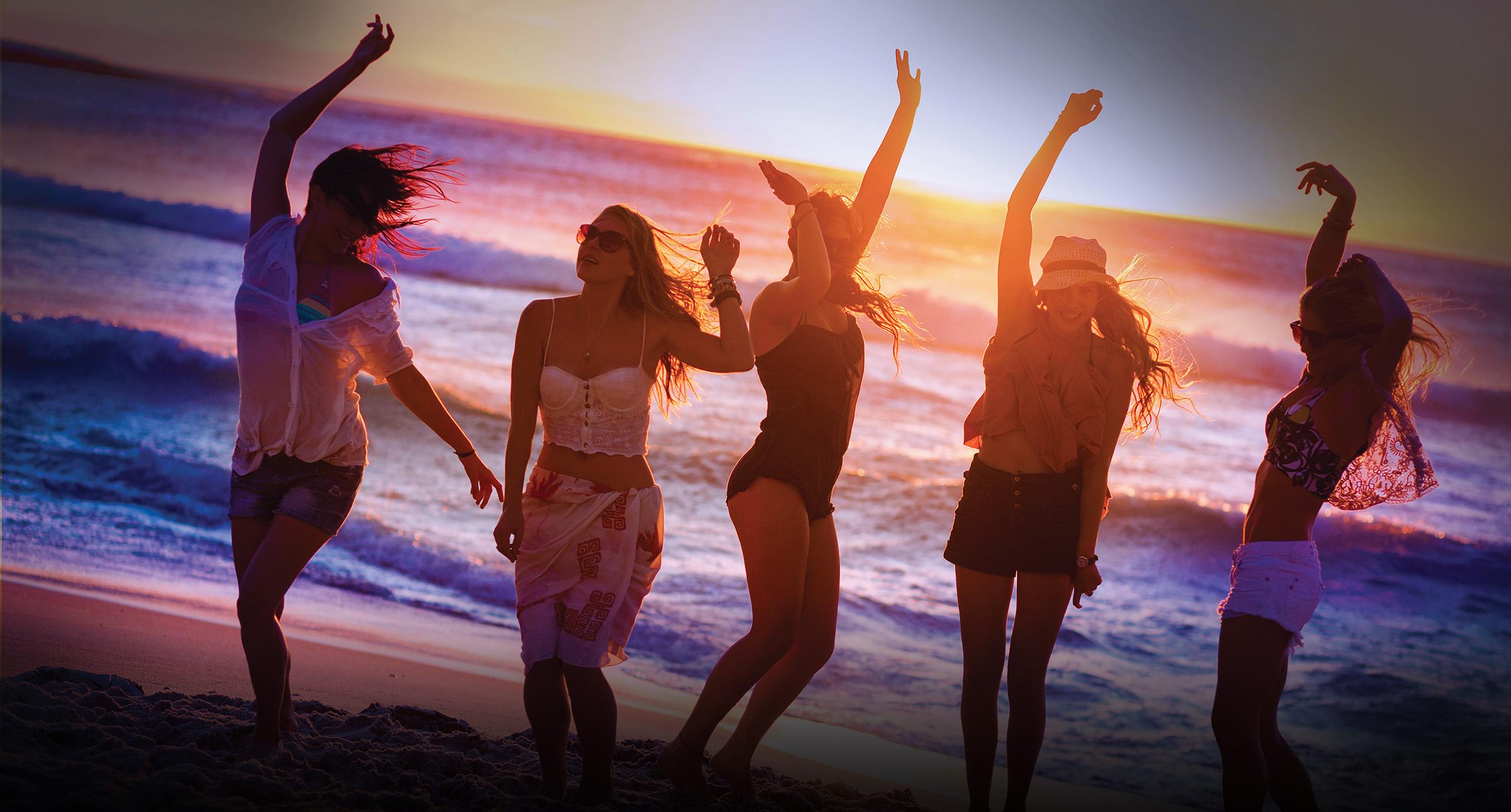 girls dancing on a beach