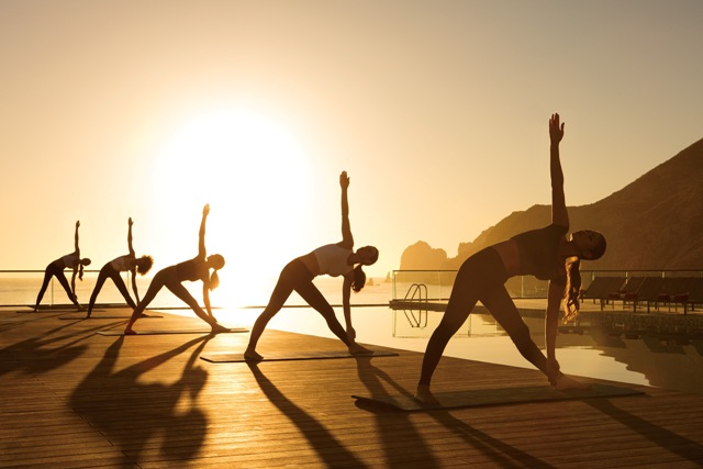 Yoga at sunrise by the pool