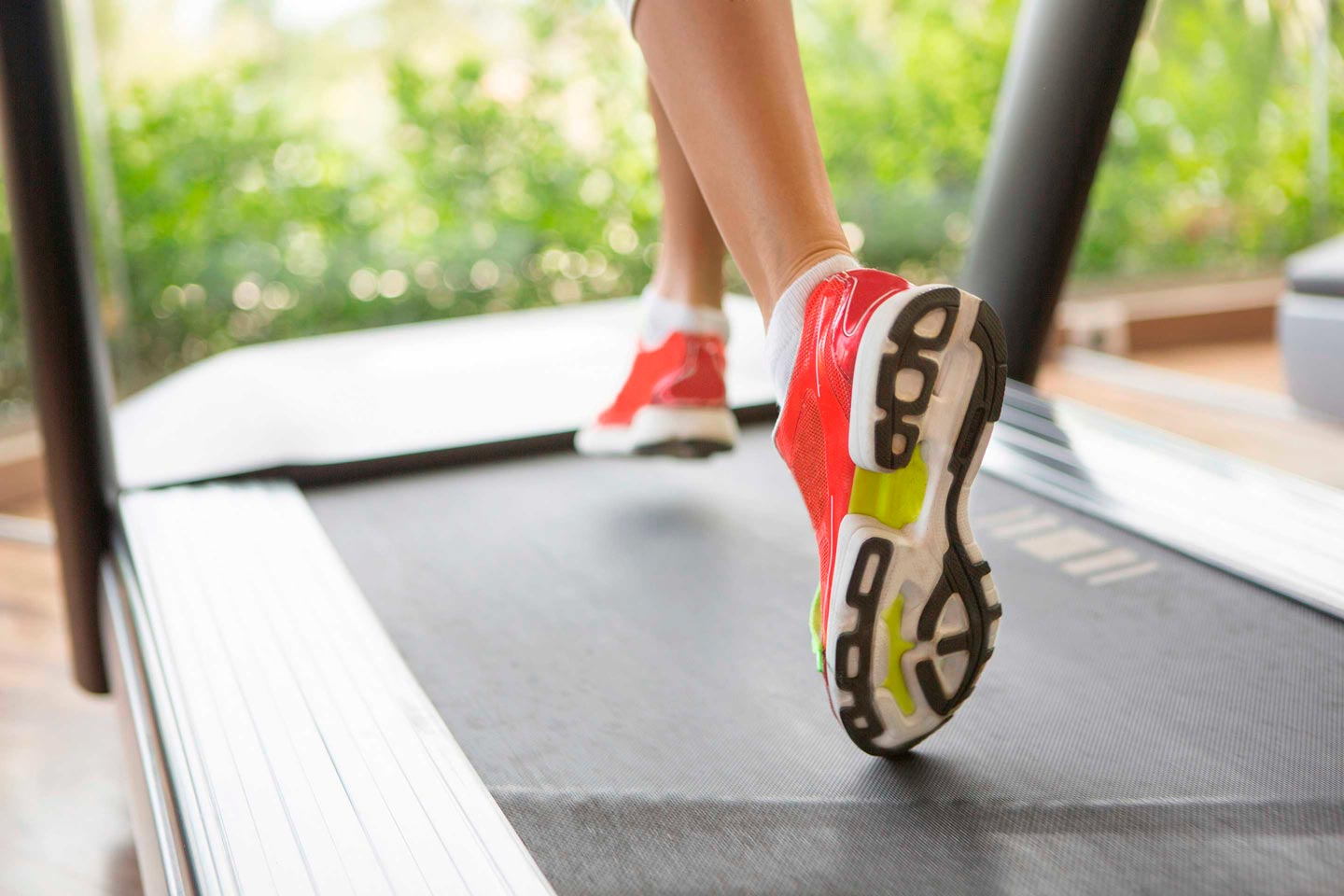 woman's feet in sneakers running on treadmill