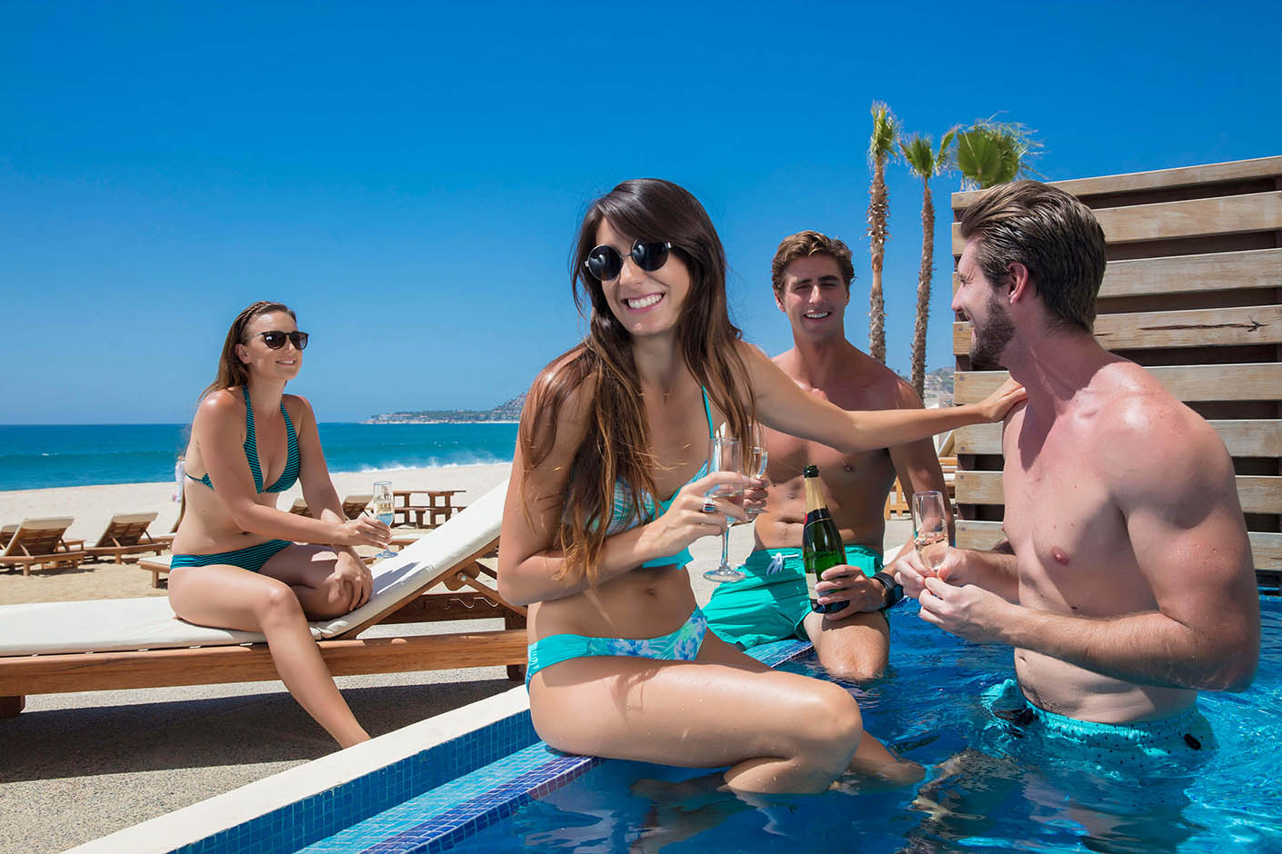 groups of friends with champagne sitting in pool