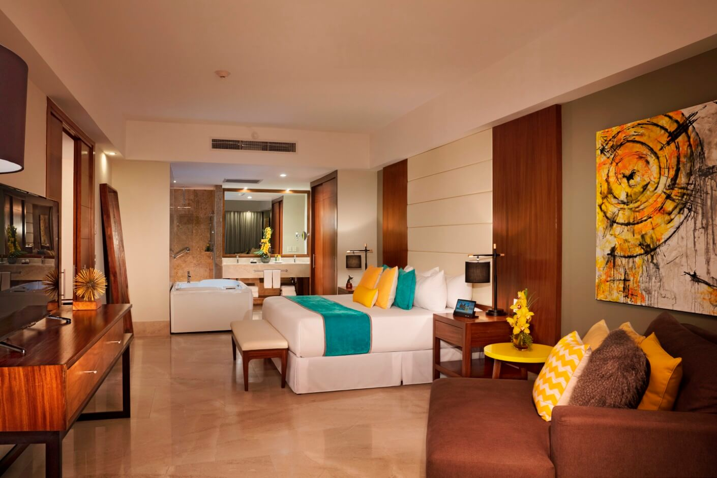 large hotel room with couch, dining table and separate bedroom