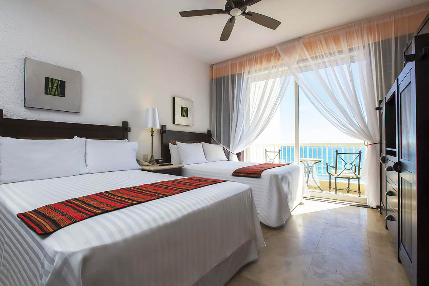 hotel room with two double beds and balcony overlooking ocean