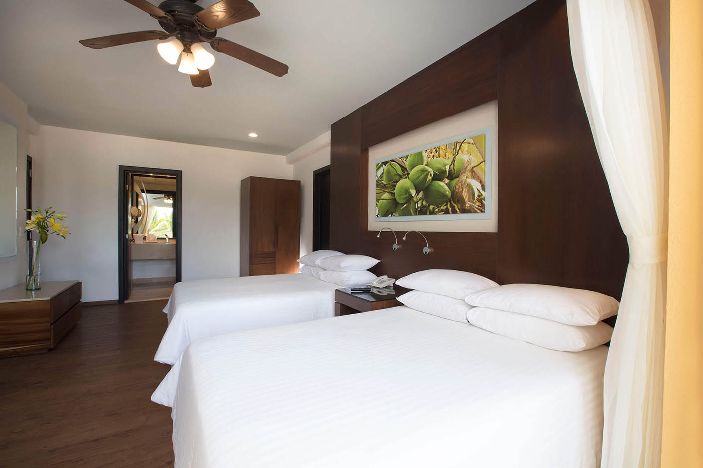 large hotel room with flat screen, kitchen table, lounge chairs and counter top