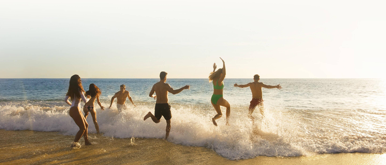 friends running into the ocean