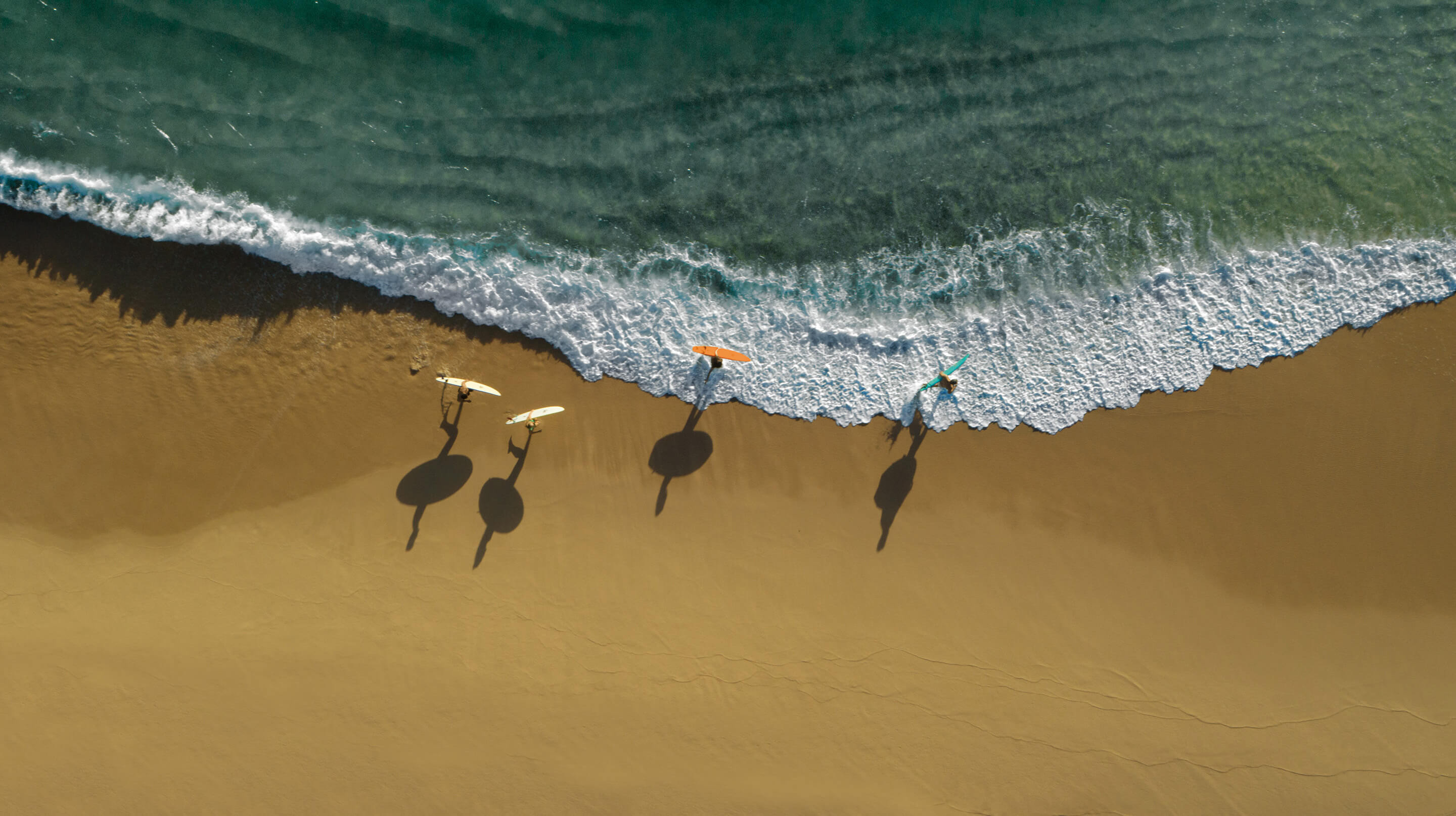 friends running down the beach with paddle boards